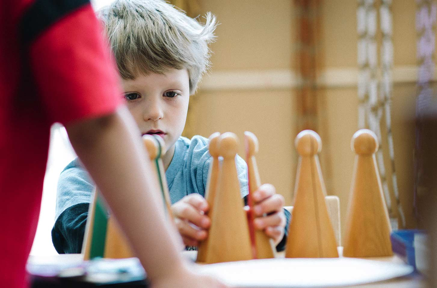 A child plays with toy cones in a classroom